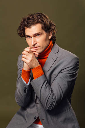 Full lengh portrait of a tall handsome man dressed in orange turtleneck, grey jacket and white jeans posing on the green background Stock Photo