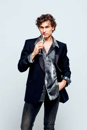 Tall handsome confident young man in a jacket holding glass of wine over white background