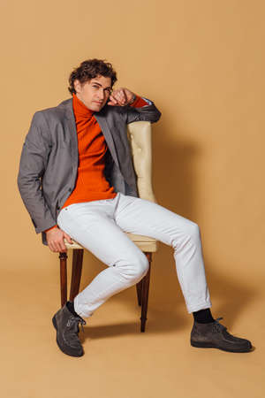 Fashion portrait of a tall handsome man dressed in orange turtleneck, white jeans and grey jacket sitting on an armchair on the beige background