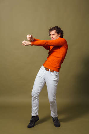 Full lengh portrait of a tall handsome man dressed in orange turtleneck and white jeans posing on the green background