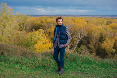 Tall handsome man walking outdoor in yellow autumn forest on the hill before storm Banque d'images