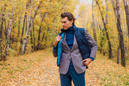 Tall handsome man dressed in a brown jacket walking in the autumn alley Banque d'images