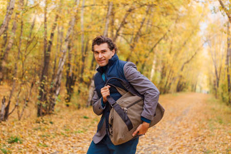 Tall handsome man dressed in a brown jacket walking with a bag in the autumn alley