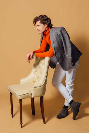 Fashion portrait of a tall handsome man dressed in orange turtleneck, white jeans and grey jacket posing with an armchair on the beige background