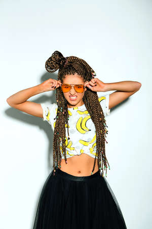 Portrait of a young stylish woman with braided hair and yellow sunglasses on the white background.