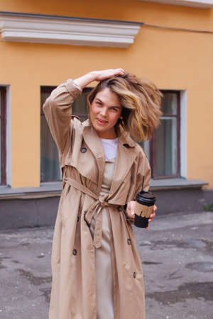 Young smiling millennial woman with wild hair dressed in an autumn coat walking with a cup of coffee to go near the old building.