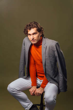 Full lengh portrait of a tall handsome man dressed in orange turtleneck, grey jacket and white jeans posing on the green background Banque d'images