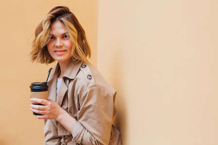 Young smiling millennial woman with wild hair dressed in an autumn coat standing a cup of coffee to go near the beige wall.