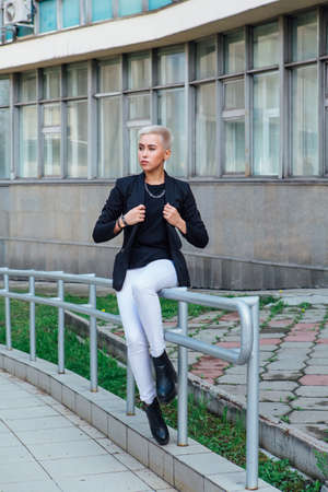 Young stylish business woman with short hair and nose piercing. Confident girl look like lesbian sitting near business center