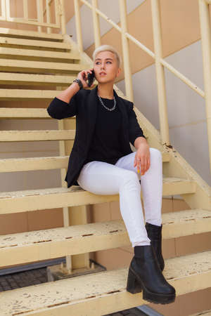 Young stylish business woman with short hair and nose piercing. Confident girl look like lesbian sitting on the stairs with mobile phone near business center