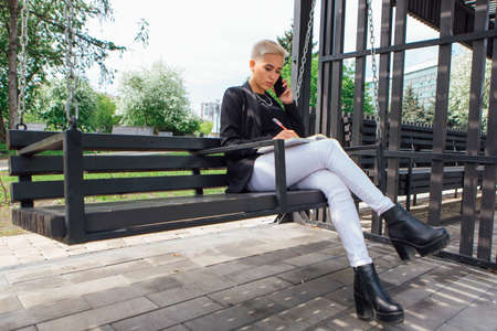 Young stylish business woman with short hair and nose piercing. Confident girl look like lesbian sitting with mobile phone on the swing Zdjęcie Seryjne
