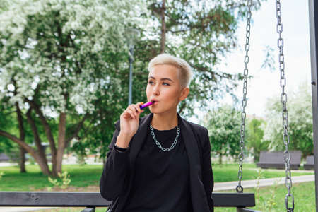 Young stylish business woman with short hair and nose piercing. Confident girl look like lesbian sitting and smoking electronic cigarette on the swing
