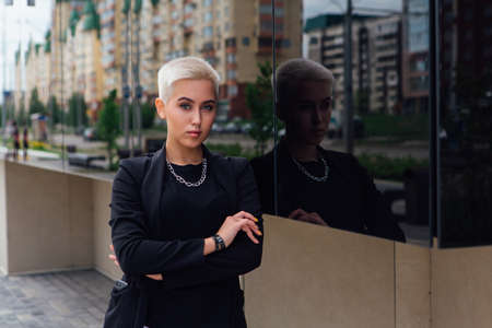 Young stylish business woman with short hair and nose piercing. Confident girl look like lesbian standing near business center with mirror walls Zdjęcie Seryjne