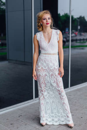 Young beautiful blond bride in white wedding dress and bright make up standing near mirror window outdoors.