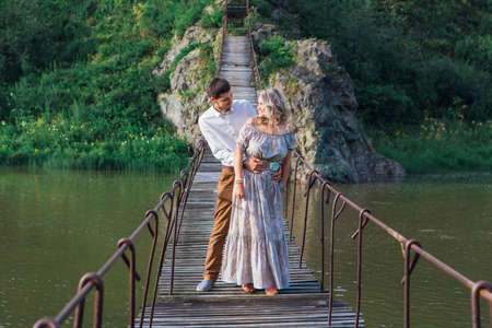Beautiful young romantic couple standing and hugging on the suspension bridge above the river Zdjęcie Seryjne