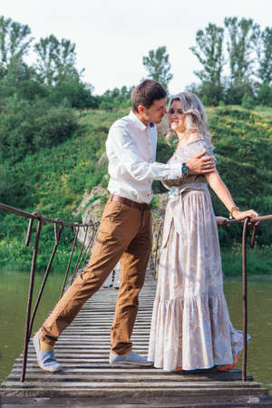Beautiful young romantic couple hugging and kissing on the suspension bridge above the river