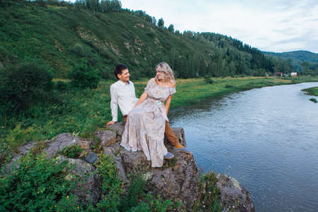 Beautiful romantic inloved couple sitting on rocks by the river. Copy space.