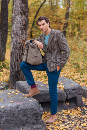 Tall handsome man dressed in a brown jacket posing with a bag near the rocks in autumn forest