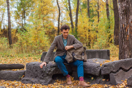 Tall handsome man dressed in a brown jacket posing with a bag on the rocks in autumn forest Zdjęcie Seryjne