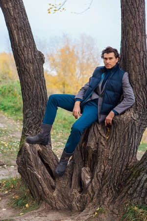 Tall handsome man climbing on the tree in yellow autumn forest Zdjęcie Seryjne