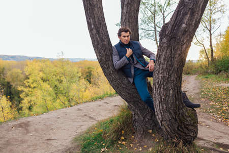 Tall handsome man standing near the tree in yellow autumn forest