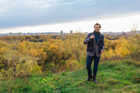 Tall handsome man walking outdoor in yellow autumn forest on the hill