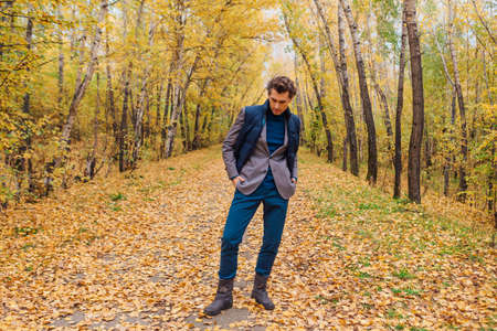 Tall handsome man dressed in a brown jacket walking in the autumn alley Zdjęcie Seryjne