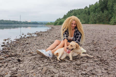 Young beautiful woman with blond curly hair sitting with her labrador retriever dog on the river shore