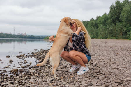 Young beautiful woman with blond curly hair huging with her labrador retriever dog on the river shore
