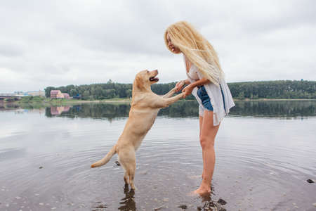 Young beautiful woman with blond curly hair playing with her labrador retriever dog in river. Zdjęcie Seryjne
