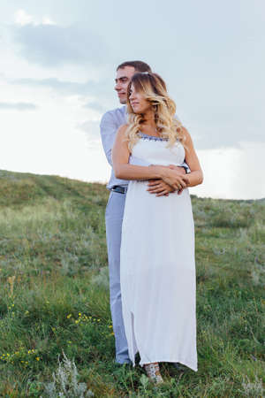 Happy young couple, expecting a baby, walking in summer rainy day on a field. Man hugs his pretty pregnant woman in a white dress. Waiting for the baby, pregnancy concept.