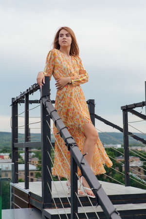 Beautiful young woman in long leopard dress standing on the stairs on the top of the roof of a building.