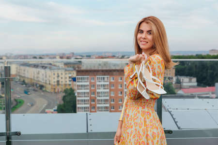 Beautiful young woman in long leopard dress standing on the stairs on the top of the roof of a building holding her white shoes in hand. Zdjęcie Seryjne
