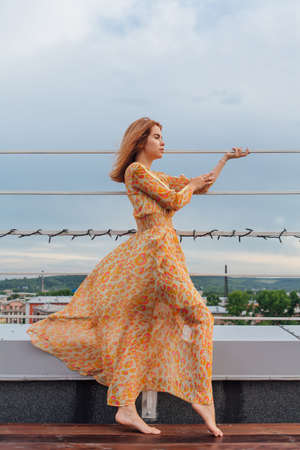 Beautiful young woman in long leopard dress standing with bare feet on the stairs on the top of the roof of a building.