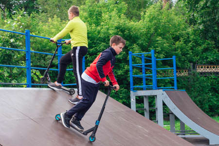 Novokuznetsk, Russia - July 19, 2021: Group of boys ride a scooter in an extreme park. Study of extreme sports on the open air. Publikacyjne