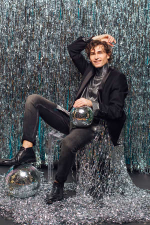 Tall attractive man sitting on the floor over the sparkle background and mirror disco ball holding glass of champagne. Party concept.