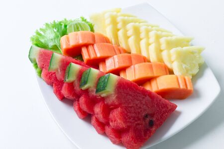 Sliced fruits for health mixed with watermelon, papaya, pineapple with vegetable and lime on white dish and white table background Archivio Fotografico