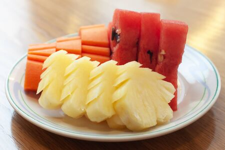 Sliced fruits for health mixed with watermelon, papaya, pineapple on white dish and wood table