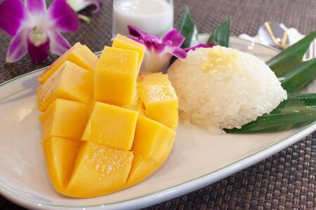 Sticky rice and sliced mango with coconut cream is Thai food dessert on white dish Archivio Fotografico