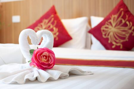 Towels folded in bird shape with pink flowers on the white bed in the bedroom with wood headboard and red Chinese style pillows.
