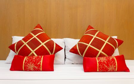 Red pillows in Chinese style put on white bed in the room with wooden on the headboard