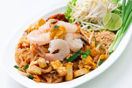 Pad Thai fried noodles with shrimps as Thai traditional spicy noodles with ingredients as shrimps, fried noodles, chili, sliced tofu, vegetable, lime, bean sprouts on white dish Archivio Fotografico