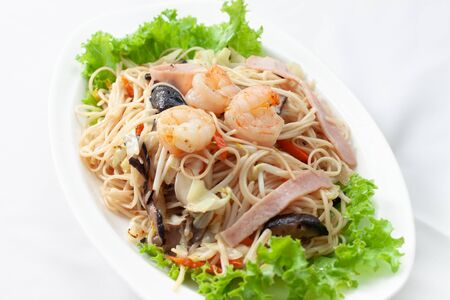 Chinese food fried noodle eating on Chinese new year celebrations ingredients with fried noodle, sliced carrot, ham, vegetable on white dish.