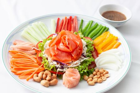 Chinese new year auspicious food (Yu Sheng) eating on celebrations ingredients with peanut, salmon, nut, red ginger, sliced carrot, sliced chili, sliced Cucumber, sliced tomato on white dish and served with sauce.