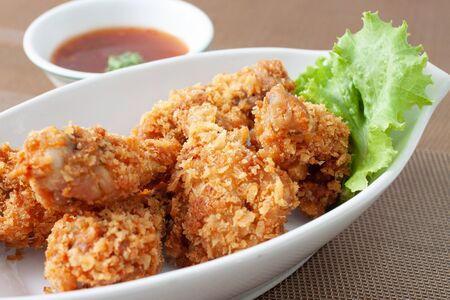 Fried chicken in white bowl served with chili sauce on brown placemat