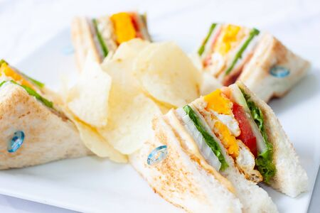 Close-up many sandwiches and chip on white dish