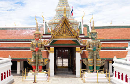 The Royal Grand Palace and Temple of the Emerald Buddha Bangkok, Thailand - June 18,2020 : Giants Tosagirithorn with a red body and Tosagirivan with a green body