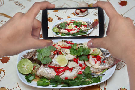 fishbone: Using mobile phone to take photo a dish of Tilapia fish streamed lemon for share to social network. Selective focus.