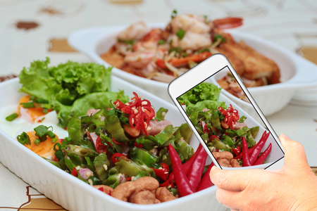 myspace: Friend using smart-phone to take photo spicy sour sausage salad for share the social network. Stock Photo