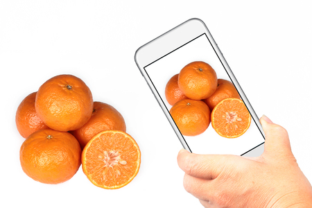 Friend using smart-phone to take photo oranges for share the social network. Stock Photo